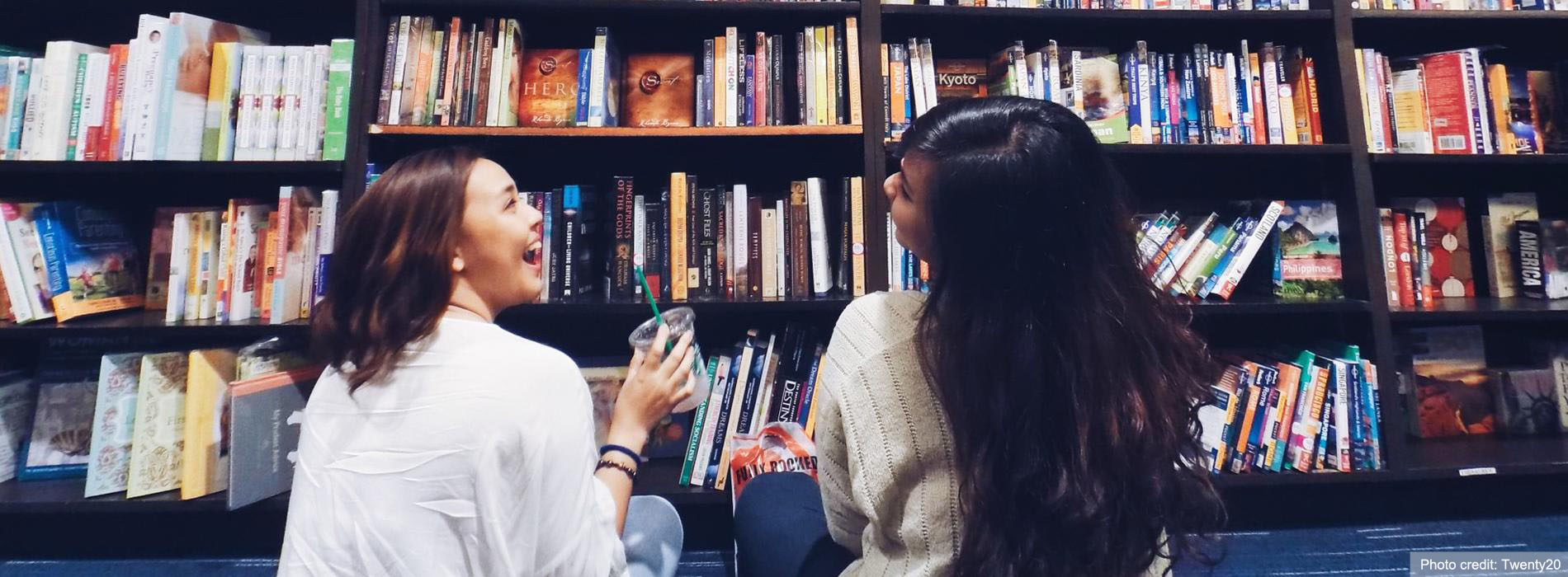 Two women sit on a library floor, laughing