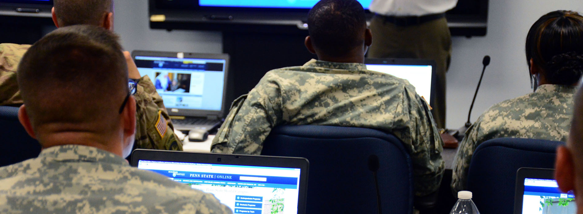 Men and women in uniform sit at computers, listening to instructor